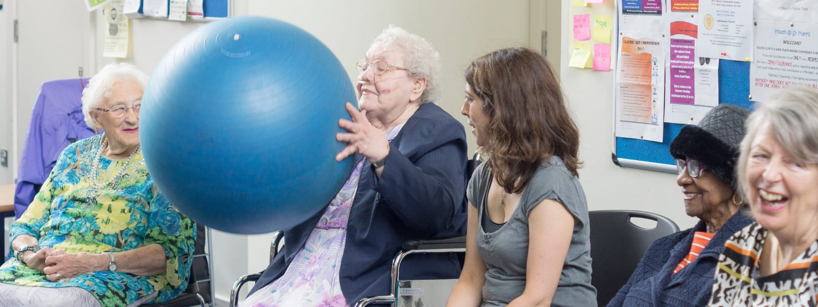 Older lady catching an exercise ball at our Golden Oldies group
