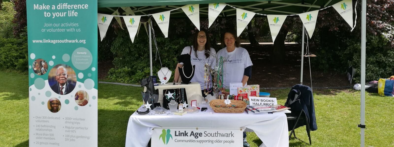 Two volunteers wearing Link Age Southwark t-shirts manning a stall